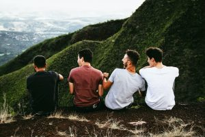 Group of four males sit and laugh on the side of a lush mountain that towers over the landscape. They are looking out over the horizon and laughing together. Open Pathways Counseling can help you through major life changes, a quarter-life crisis, and more. Contact us today for the support you deserve.
