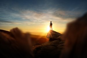 Man stands on lone rock formation in the distance, as the sun rises behind him. This image can describe what it feels like to overcome your anxiety, and Open Pathways Counseling can support you! We offer anxiety therapy in Columbus, OH. Contact us today for the anxiety treatment you deserve!