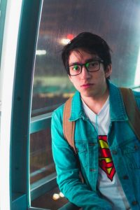 Portrait of young adult man leaning against a window. He's wearing a backpack and a teal button up shirt, looking at the camera. A Superman symbol can be seen on his undershirt. He has low self-esteem because of his adult adhd symptoms, but Open Pathways Counseling offers the counseling for men in Columbus, OH he needs. We offer CBT for adult adhd in columbus, oh, adhd therapy in columbus, oh, and other services! Contact us today to get connected to act therapy for adhd with an adhd therapist in columbus, oh