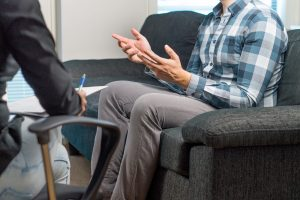 Close up of man gesturing with his hands as their therapist listens. They appear to be meeting with an adult ADHD therapist in Columbus, OH to address their ADHD symptoms and surrounding anxiety. Focused Mind ADHD Counseling offers anxiety therapy in Columbus, OH, ADHD treatment for adults, and more.