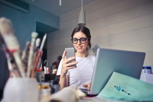 A busy woman smiles as she checks her phone after working on her laptop. She is happy that she's finally found the right adhd therapist in columbus ohio. Focused Mind ADHD Counseling offers adult ADHD treatment in Columbus, OH, Columbus therapy, and more.