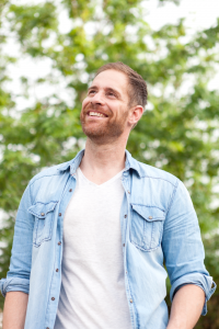 Portrait of man in opened button up shirt smiles as he looks off to the left with a tree in the background. His cheerful expression and smiling eyes are due to attending counseling for depression. Open Pathways Counseling offers depression counseling in columbus, oh. If you are experiencing anhedonia, feeling lost, feeling hopeless, or any other signs of depression, contact us today!