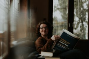 Woman sits at table as she looks out the window. She has a book in her hands about graduate school options. She isn't letting adhd get in the way of her dreams. Focused Mind ADHD Counseling offers adult adhd treatment in columbus, oh, cbt for adult adhd in columbus, oh, online adhd therapy in ohio, and more.