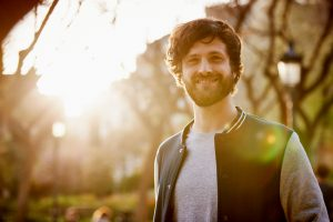 Man with beard in letterman jacket smiles at the camera as the sun sets behind him. He is happy that he's found an adult ADHD specialist in Columbus, OH. Contact Focused Mind ADHD Counseling for adult ADHD treatment, and more.
