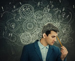 Man holds pencil to his head as illustrated gears clutter around his busy mind. He appears to be struggling with sorting his thoughts. Contact Focused Mind ADHD Counseling to get in touch with a therapist in Columbus Ohio that can support you with adult ADHD therapy and more.