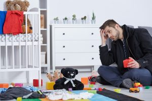 A man sits on the floor of a toddlers room. He looks concerned as he holds a toy block against his head, and is worried that his adult ADHD will keep him from getting his life together. He is an adult with ADHD, and Focus Mind ADHD Counseling offers counseling for men with ADHD in Columbus, OH. Contact us today for support with attention deficit hyperactivity disorder in adults, treatment for ADHD in adults, and more.