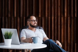 Man with glasses sits at a table with coffee cup in hand. He is happy because he has been working through counseling for men with ADHD in Columbus, OH. Focused Mind ADHD Counseling offers therapy for men with ADHD in Columbus, OH, counseling for men's issues, and more. Contact us today for the support you deserve!