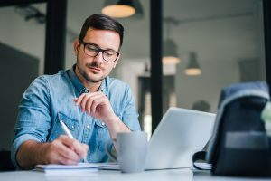 Man with glasses writes something in his notebook as. He is searching for an adhd psychologist in columbus, oh. Focused Mind ADHD Counseling offers adult adhd treatment in columbus, oh, online adhd therapy in ohio, and more.