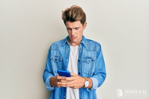 A young adult man in a denim button up appears focused on his phone screen. He appears disappointed by what he is reading. This could symbolize the pain of rejection one might experience when texting a crush. We offer support for rejection sensitive dysphoria treatment in Columbus, OH. Contact us for RSD ADHD treatment, ADHD treatment for adults, and other services.