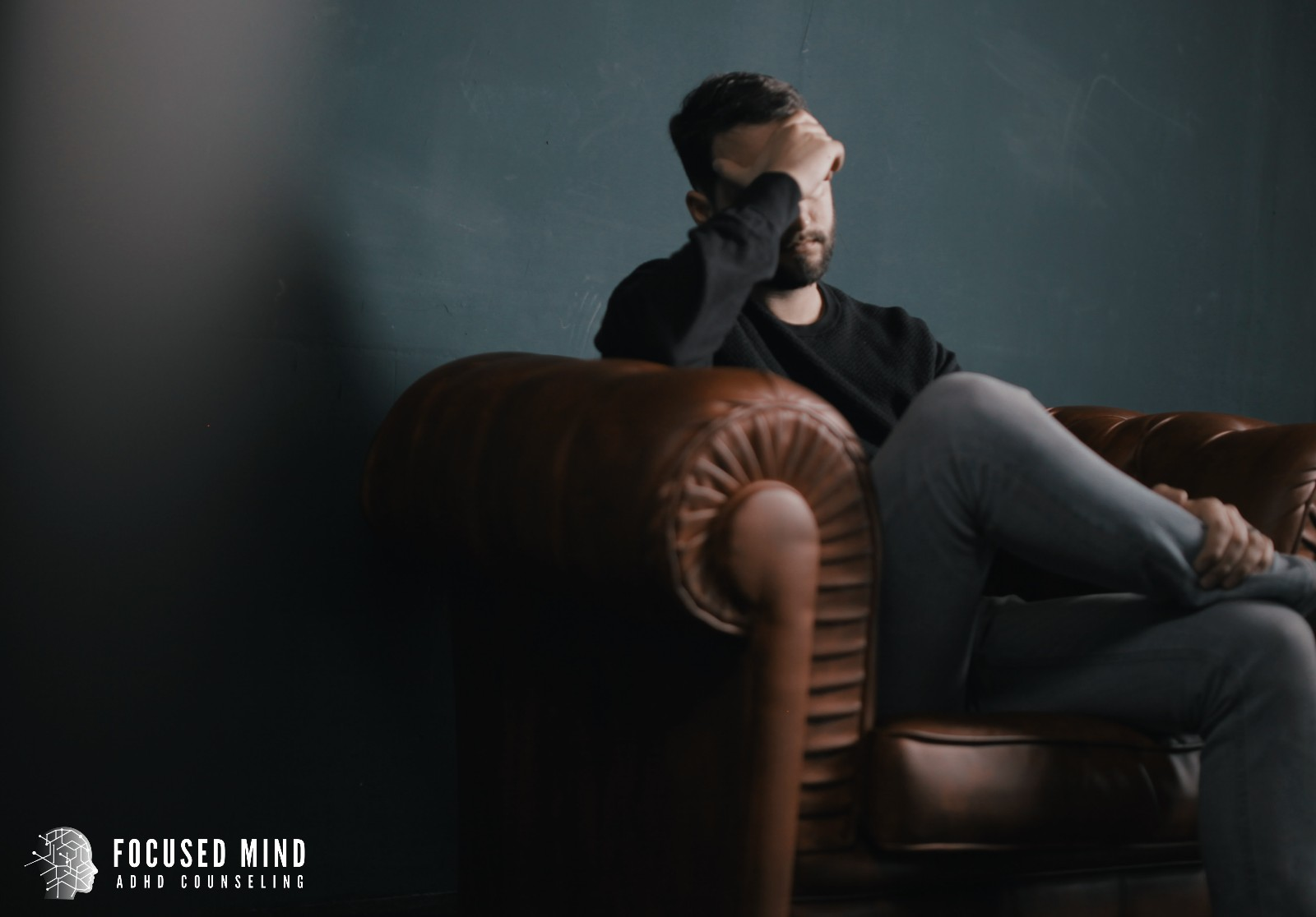 A man crosses one leg over the other as he sits in an armchair. He appears upset, and is resting his hand against his forehead. This could symbolize the pain of rejection. We offer similar support with rejection sensitive dysphoria treatment in Columbus, OH. Contact Focused Mind ADHD Counseling for ADHD treatment for adults, RSD ADHD treatment, and other services.