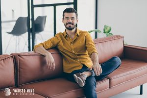 A man casually smiles as he sits on a sofa in an office. He appears joyful, collected, and calm. This could symbolize an adult who completed adult ADHD treatment in Ohio. Contact an adult ADHD specialist in Columbus, OH for adult ADHD treatment today.