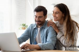 A couple smile as the man types on his laptop. His partner appears happy as she looks over his shoulder at the screen. This could symbolize how relationships may be improved by adult ADHD treatment in Ohio. Contact Focused Mind ADHD Counseling to get in touch with an adult ADHD specialist today.