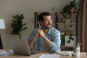 A smiling man sits and rests his elbows on the table in front of him. He appears to be taking a break from work on his laptop. This could symbolize how an adult with ADHD symptoms in ohio could feel empowered after starting adult ADHD treatment in Ohio. Focused Mind ADHD Counseling offers support with ADHD in adults. Contact an adult ADHD specialist today!