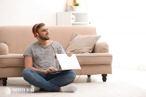 Young adult sits on the floor as he listens to something on his laptop. He is an adult with ADHD, and is wearing headphones to drown out any other distractions. We provide adult ADHD treatment to help you recognize how your ADHD symptoms can be used to your advantage. Contact an adult ADHD specialist for support today.