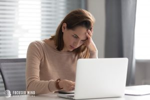 A woman sitting at a table appears annoyed as she reviews something on her laptop screen. This could symbolize the confusion that comes from misunderstanding an online adult ADHD quiz. Focused Mind ADHD Counseling offers ADHD testing in Columbus, OH to help you better understand your adult ADHD symptoms. Contact an adult ADHD specialist in Columbus, OH today!
