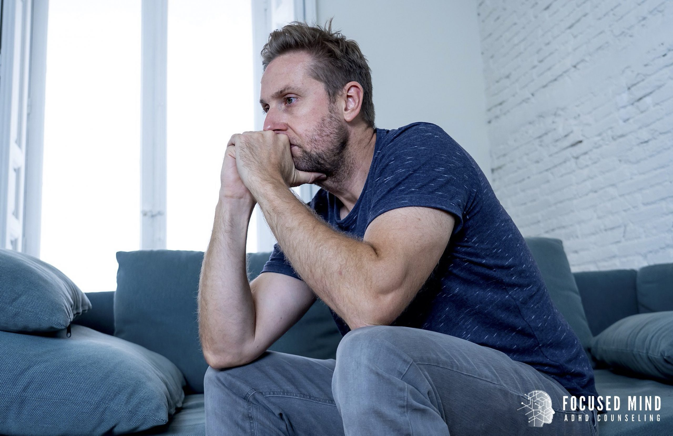 A man sits with his hands against his mouth as he thinks. This could represent the strong emotions that come with Adult ADHD. Contact Focused Mind ADHD Counseling for emotional regulation therapy in Columbus, OH. An adult ADHD specialist for more info about ADHD in adults.