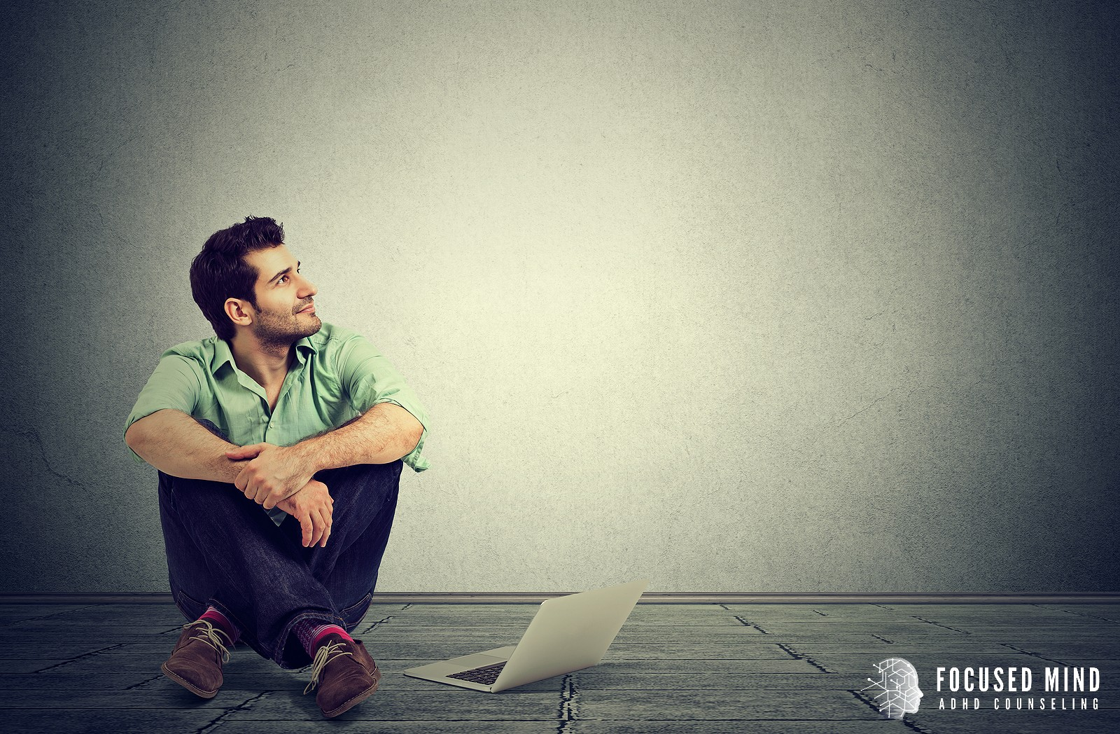 A man looks up to the side as he sits on the ground next to a laptop. This could represent the calmed mind of a client after treatment for adult ADHD in Columbus, OH. Contact an adult ADHD therapist in Ohio for an adult ADHD quiz, online therapy, and other services.