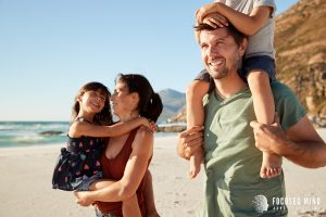 A happy family of 4 smiles as they walk along the beach. This could represent the overwhelming happiness that might be felt by adults with ADHD. Focused Mind ADHD Counseling offers emotional regulation therapy in Columbus, OH. Contact an adult ADHD specialist for more information on ADHD and emotional regulation.