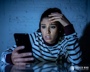 A holds her phone with a concerned look on her face. This could represnt the overwhelming emotions felt from an adult with ADHD. Contact Focused Mind ADHD Counseling for emotional regulation therapy in Columbus, OH and other services! An adult ADHD specialist would be happy to help!
