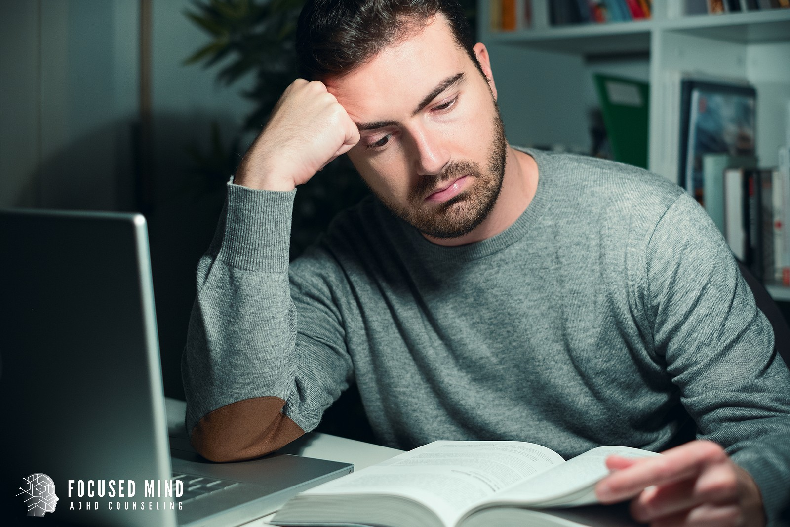 a man resting his head against his hand appears tired as he reads. ADHD therapy in Columbus, OH can provide support for concentration. Learn more about our adult ADHD quiz from an adult ADHD therapist in Ohio.