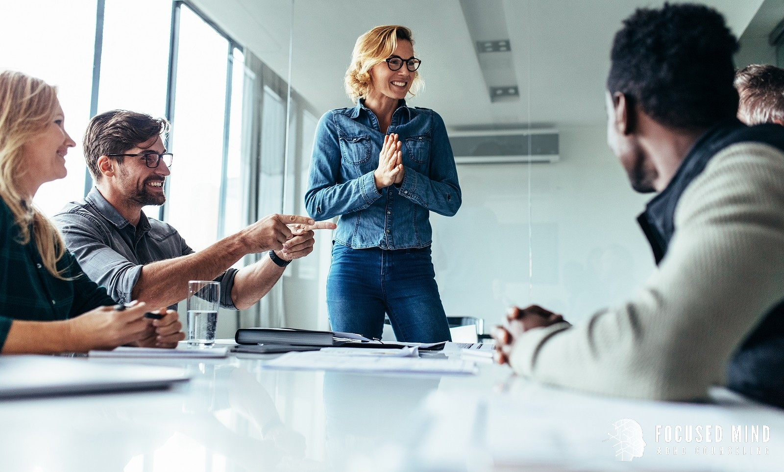 A woman smiles as she address a board room. This could represent ADHD superpowers at work. Contact Focused Mind ADHD Counseling to learn about cognitive behavioral therapy for adult adhd in Columbus, OH and other services.