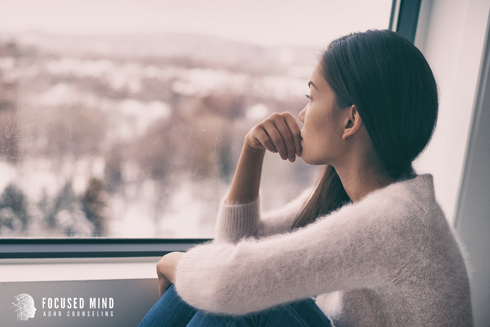 A young woman looks out a window with a concerned look. This could represent negative ADHD symptoms clouding one's mind. Focused Mind ADHD Counseling offers support with ADHD testing in Columbus, OH. Learn more about our adult ADHD quiz today!