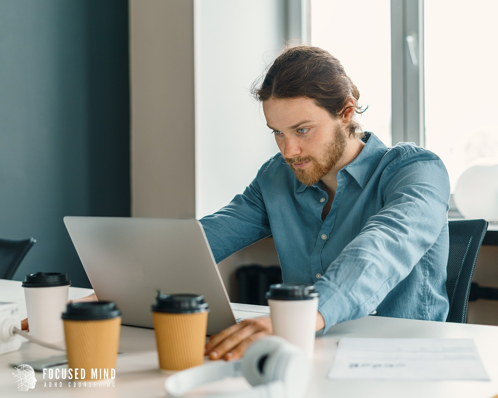 A man sits at a table with multiple coffee cups scattered. This represents how ADHD and workaholism can overtake one's attention. Focused Mind ADHD Counseling can help you overcome ADHD and hyperfocus in Columbus, OH. Contact a therapist in Columbus Ohio for support today!
