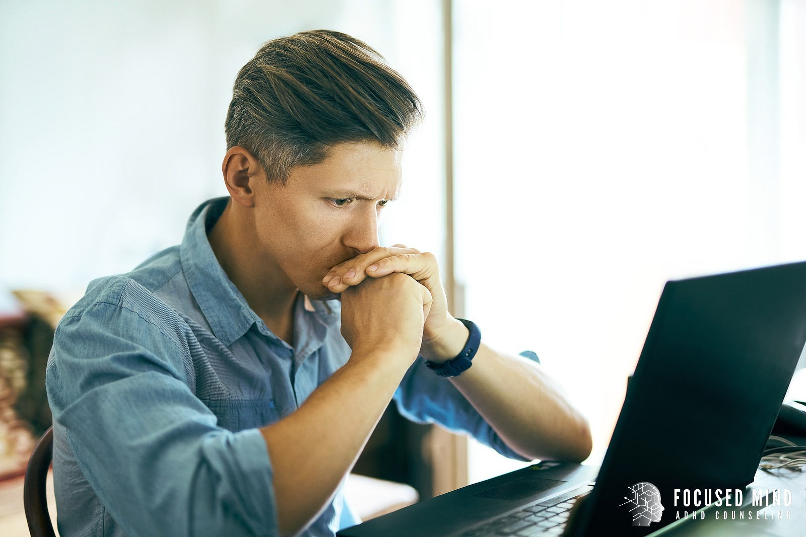 A man sits with a pensive look as he stares at his laptop. ADHD and perfectionism can go hand in hand. Contact Focused Mind ADHD Counseling for support with ADHD symptoms. A therapist in Columbus Ohio can provide support today!