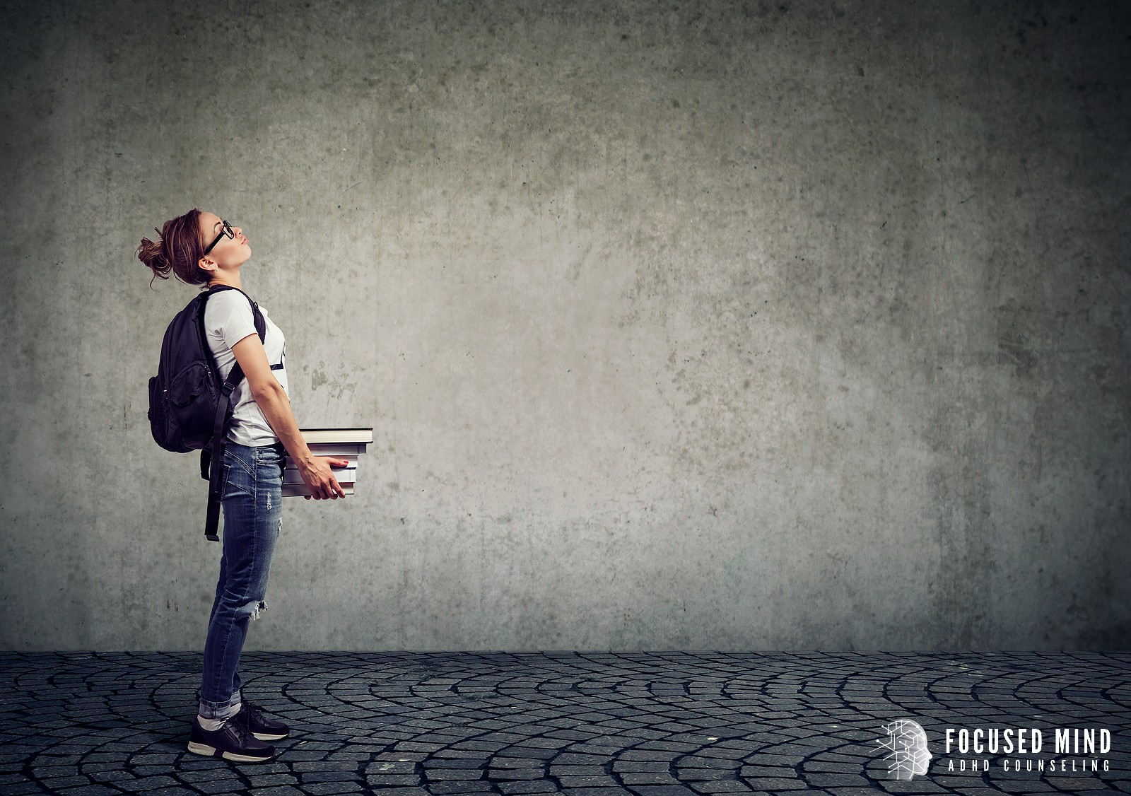 A student holds textbooks in hand as they appear to struggle with the weight. This could represent the weight of anxiety related ADHD. Learn more about our adult ADHD quiz by contacting Focused Mind ADHD Counseling today! 43017   43016   43220
